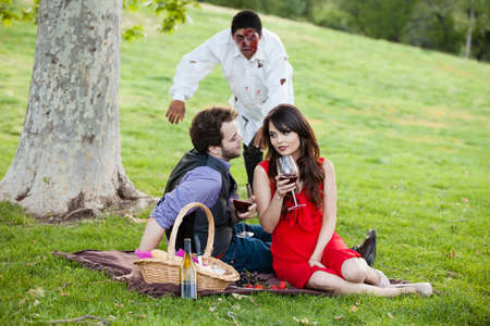 Beautiful Young  Engagement Couple on a picnic unaware of Zombies approaching photo