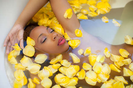 Beautiful young woman pampering her self with a milk and rose petal bath photo