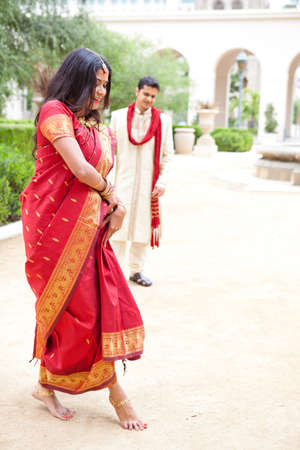 Gorgeous Indian bride dancing as her husband looks on photo