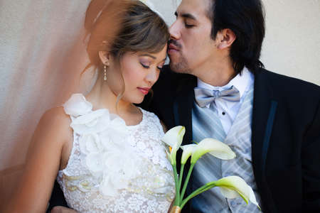 filipino adult: Tender moment between a beautiful Bride and Groom Mixed Ethnicity