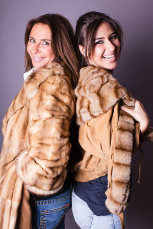 Beautiful Young Mother and Daughter on Mothers Day in jeans and Fur coats photo