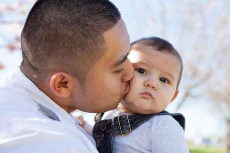 hispanic boy: Padre latino joven que besa a su hijo Foto de archivo