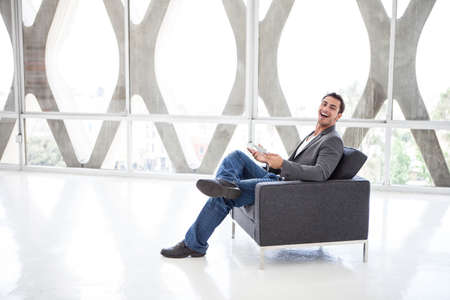 Attractive business man in his 20s working on a mini think pad in a wide open space Standard-Bild