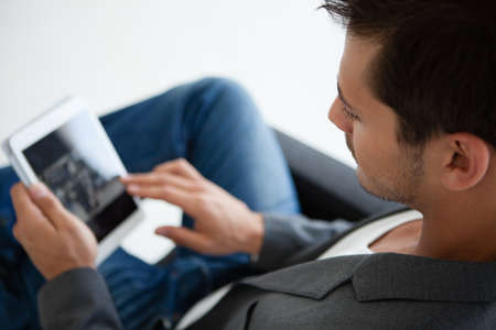 Close up croped image of an Attractive business man in his 20s working on a mini think pad Standard-Bild