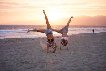 playing in the sea: Sunset with Two Beautiful Woman doing cartwheels on the Beach in Santa Monica California