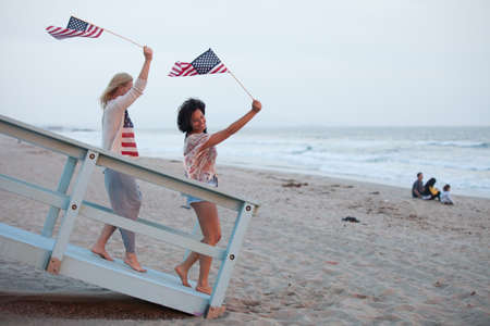 union beach: Woman on the 4th of July at the Beach with USA flags American youth concepts Stock Photo