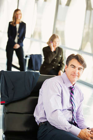 Man and two mature business women in a cellular meeting in a modern building photo