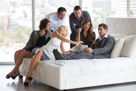 Groep jonge diverse etniciteit mensen om samen na het werk voordat een feestje lsharing ideeën op een mini touchpad