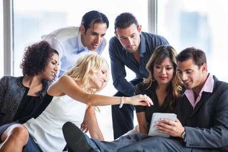 Group of young diverse ethnicity people getting together sharing ideas on a mini touch pad Stock Photo - 19731576