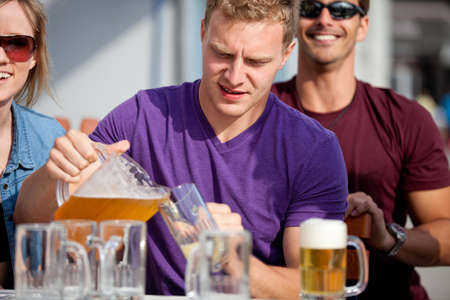 Attractive Man pouring a beer at an outside cafe on the Beach in Venice California photo