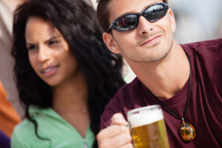 Attractive Man and woman with a beer at an outside cafe on the Beach in Venice California photo