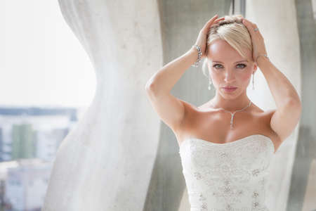 Gorgeous blond bride framed in a Pent house window of a modern hotel