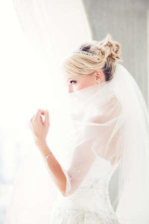 Herrliche lächelnde blonde Braut vor einem Penthouse Fenster in einem modernen Hotel Höchststand über ihren Schleier
