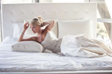 Beautiful Blonde Bride on a Bed at a hotel Stock Photo