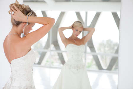 penthouse: Elegant Reflection of a Beautiful blond bride in mirror in modern glass building penthouse