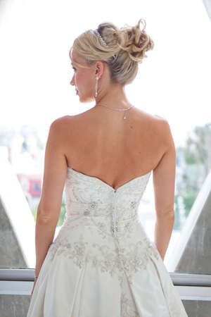 Elegant back view of a Beautiful blond bride in a modern glass hotel room penthouse suite photo