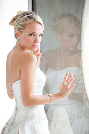 Elegant Reflection of a Beautiful blond bride in window in modern glass building penthouse Standard-Bild
