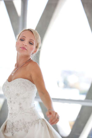 penthouse: Elegant Beautiful blond bride dancing in window of a modern glass building penthouse Stock Photo