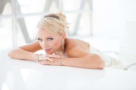 Gorgeous blond bride  in front of a Penthouse window at a modern hotel photo