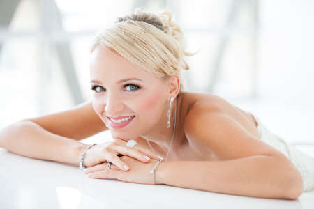 beauty shot: Gorgeous smiling blonde bride  in front of a Penthouse window at a modern hotel Stock Photo