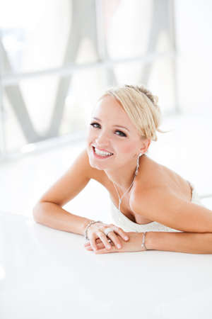 penthouse: Gorgeous smiling blonde bride  in front of a Penthouse window at a modern hotel Stock Photo