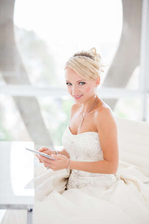 penthouse: Gorgeous smiling blonde bride  with a Mini touch pad in a Penthouse  at a modern hotel messaging her Husband I Love You!