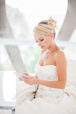 designer chair: Gorgeous smiling blonde bride  with a Mini touch pad in a Penthouse  at a modern hotel messaging her Husband I Love You!