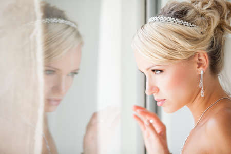 Elegant Reflection of a Beautiful blond bride in mirror in modern glass building penthouse