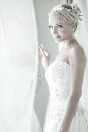 Beautiful blond bride in window at a modern glass building penthouse black and white image photo
