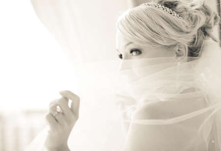 traditional dress: Gorgeous smiling blonde bride  in front of a Penthouse window at a modern hotel peaking over her veil