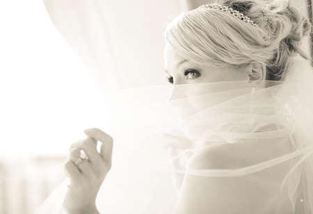 Prachtige lachende blonde bruid in de voorkant van een penthouse raam in een modern hotel met een piek boven haar sluier