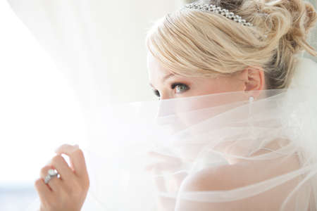 veil: Gorgeous smiling blonde bride  in front of a Penthouse window at a modern hotel peaking over her veil