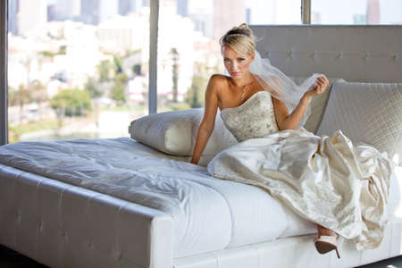 long gown: Beautiful Blonde Bride on a Bed at a hotel Stock Photo