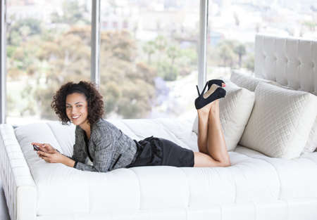 hotel bedroom: Beautiful Business Woman in a Penthouse Suite at a Hotel on her cell phone