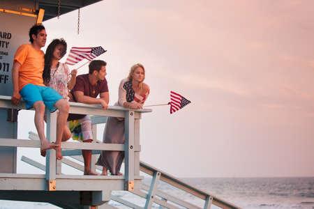 Jeune groupe d'amis à la plage au coucher du soleil avec des drapeaux américains Banque d'images - 19944072