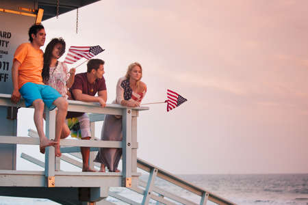 Young Group of Friends at the Beach at Sunset with American Flags photo