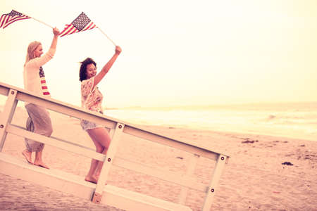labor union: Woman on the Beach at sunset  with USA flags American youth concepts