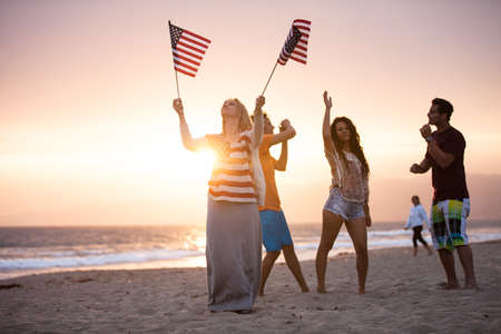 Group of Friends in their twenties dancing on the Beach at Sunsrt on 4th of July