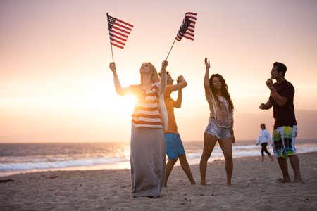 Groep van vrienden in hun twintiger jaren dansen op het strand bij Sunsrt op 4 juli