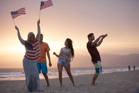 Group of Friends in their twenties dancing on the Beach at Sunset on 4th of July photo