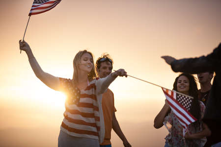 usa patriotic: Group of Friends in their twenties dancing on the Beach at Sunset on 4th of July
