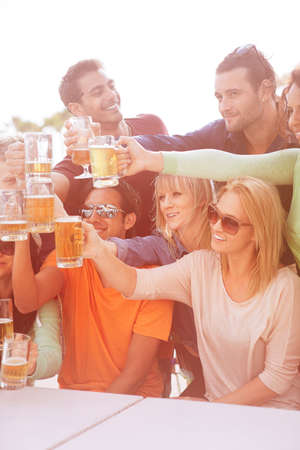 young adult: Group of Attractive young People toasting with a delicious Pale Ale  Beer