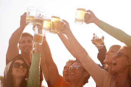 hombre tomando cerveza: Grupo de personas atractivas j�venes brindando con una deliciosa cerveza