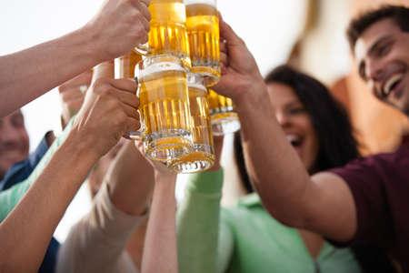 man drinkt bier: Groep van aantrekkelijke jonge mensen toasten met een heerlijke Pale Ale Beer Stockfoto