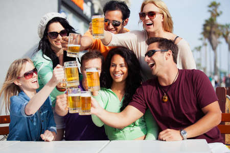 Young People in their twenties on the Venice Beach boardwalk in California drinking beer photo