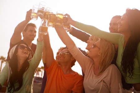 hombre tomando cerveza: Puesta de sol en el paseo mar�timo con sus amigos en la playa animando con la cerveza en un Bistro