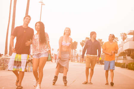 blading: Young People in their twenties walking and roller blading on the Venice Beach boaardwalk
