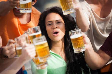 jovenes tomando alcohol: Mujer joven atractiva que tuesta con una deliciosa cerveza Pale Ale Foto de archivo