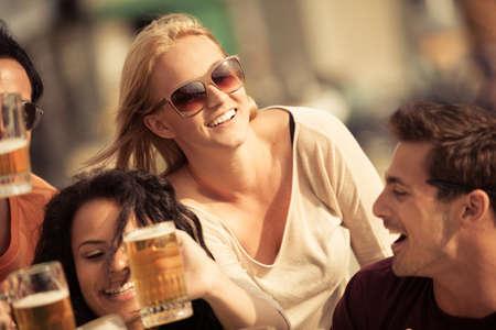 hombre tomando cerveza: Mujer joven atractiva que bebe una cerveza en un hermoso d�a soleado con amigos