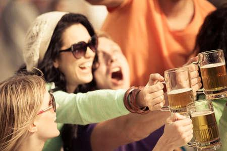 jovenes tomando alcohol: Mujer joven atractiva que bebe una cerveza en un hermoso d�a soleado con amigos